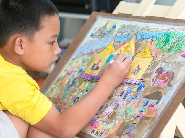 Le gamin asiatique dessine et peint son art, son aquarelle et sa couleur crayon sur papier.