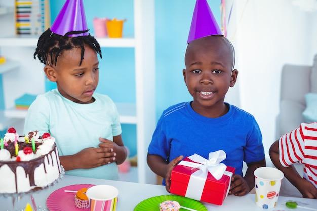Gamin excité bénéficiant d'une fête d'anniversaire en regardant la caméra