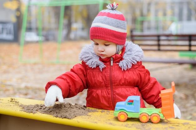 Le gamin joue des voitures dans la rue