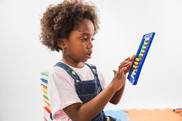 Gamin mignon avec abacus en studio