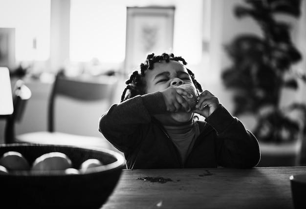 Gamin noir mangeant des fruits