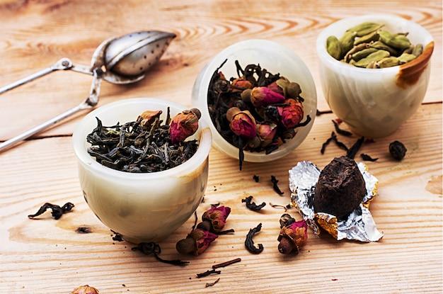 Gamme de différentes variétés de feuilles de thé sur fond en bois