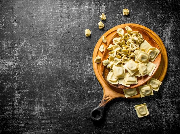 Gamme de différents types de pâte crue sur table rustique sombre.