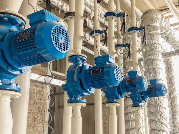 Une gamme de pompes à eau électriques bleues. tubes et moteurs dans l'industrie