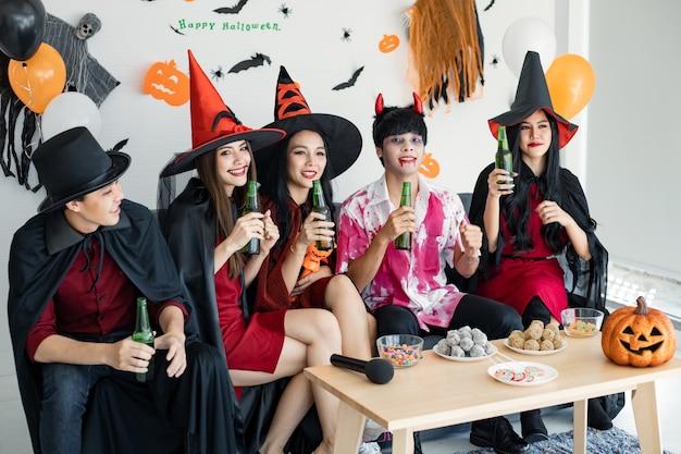 Gang de jeunes asiatiques en costume de sorcière, sorcier avec fête d'halloween pour danser et boire et ivre dans la chambre. groupe teen thai avec fêter halloween. fête de concept halloween à la maison.