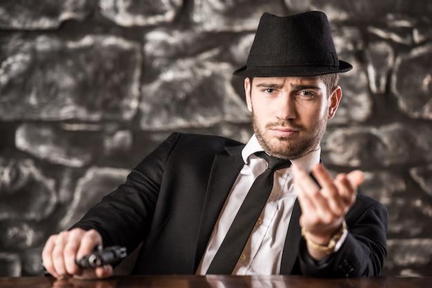 Un gangster au chapeau est assis à la table avec une arme à feu.