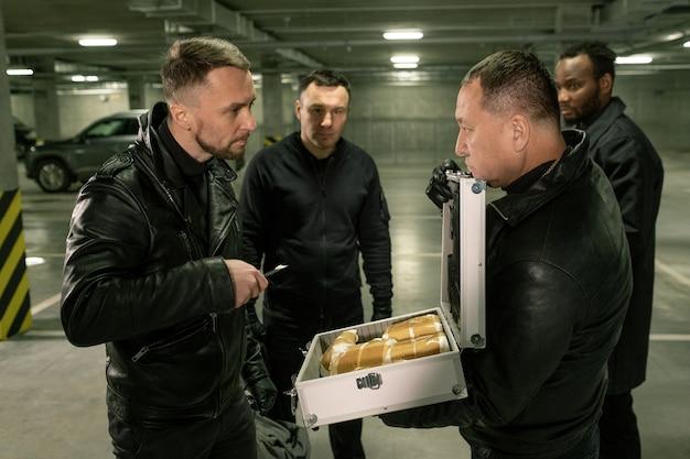 L'un des gangsters avec dose regardant un autre criminel avec de la cocaïne dans une valise ouverte tout en s'entendant sur l'aire de stationnement