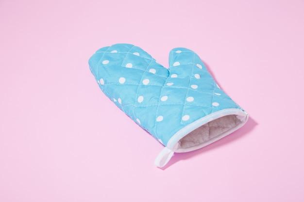 Gant de cuisine en pointillé bleu sur une surface rose isolée