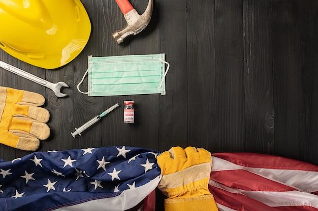 Gant d'outils de travail de constructeur de coronavirus d'évasion heureuse de la fête du travail tenant le drapeau américain de gripp