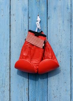 Gants de boxe en cuir rouge accrochés à un clou