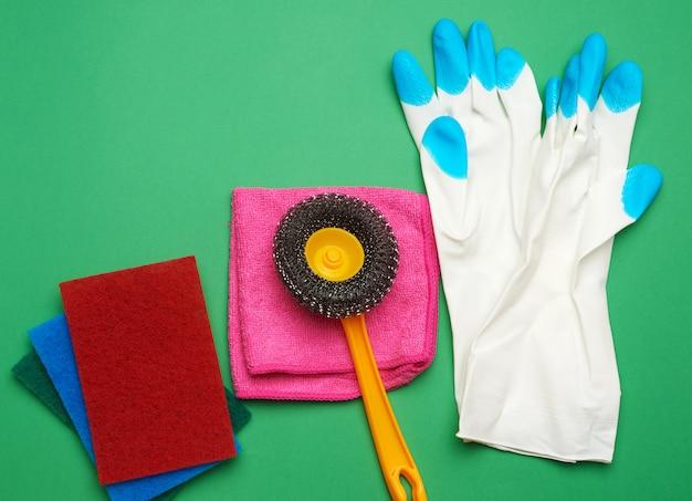 Gants en caoutchouc blanc pour le nettoyage, éponges multicolores, brosses sur fond vert, pose à plat
