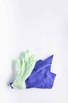 Gants en caoutchouc et chiffon en microfibre pour le nettoyage sur fond clair.
