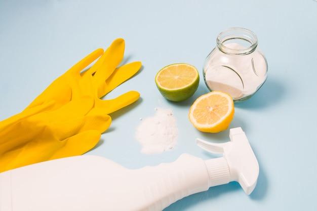 Des gants en caoutchouc, un flacon de spray blanc sans étiquette, un demi citron et citron vert, du soda renversé et un bocal en verre de soda