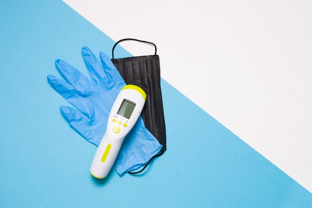Gants en caoutchouc jetables, masque facial, thermomètre infrarouge sans contact sur bleu