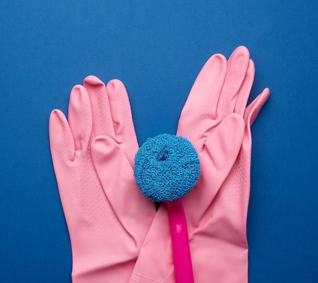 Gants en caoutchouc rose pour le nettoyage, brosses sur fond bleu