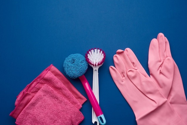 Gants en caoutchouc rose pour le nettoyage, éponges roses, brosses sur fond bleu