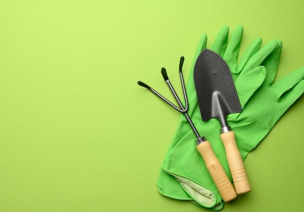 Gants en caoutchouc vert et ensemble de jardin de pelles, râteaux, fourches sur fond vert, vue du dessus, mise à plat