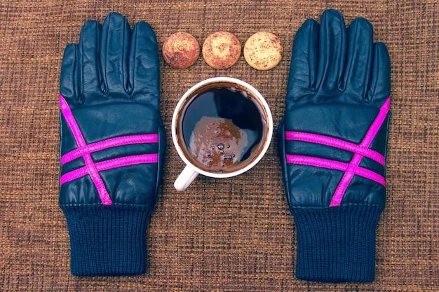 Gants en cuir à côté d'une tasse de café chaud. boissons chaudes