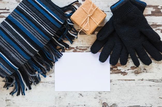 Gants et écharpe près du cadeau et de la feuille de papier