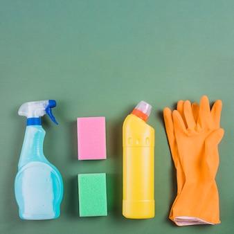Gants, une éponge et des bouteilles en plastique sur fond vert