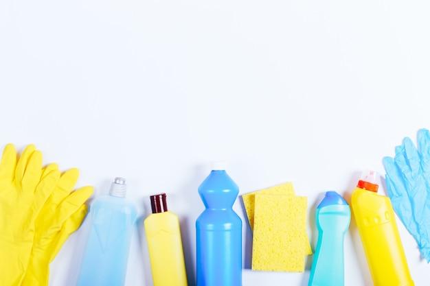 Gants, éponges, bouteilles de liquides de nettoyage sur une table blanche, espace pour le texte