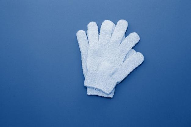 Gants exfoliants pour femme à utiliser sous la douche pour le massage et le gommage tonique dans la couleur bleue classique à la mode de l'année 2020.