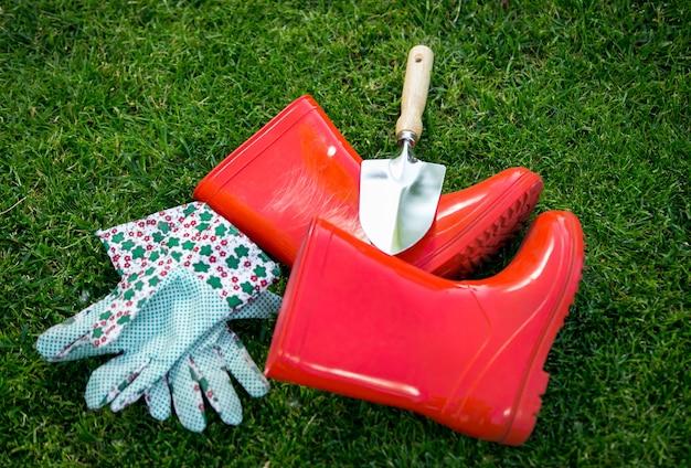 Gants en gros plan, bottes en caoutchouc et pelle sur l'herbe verte