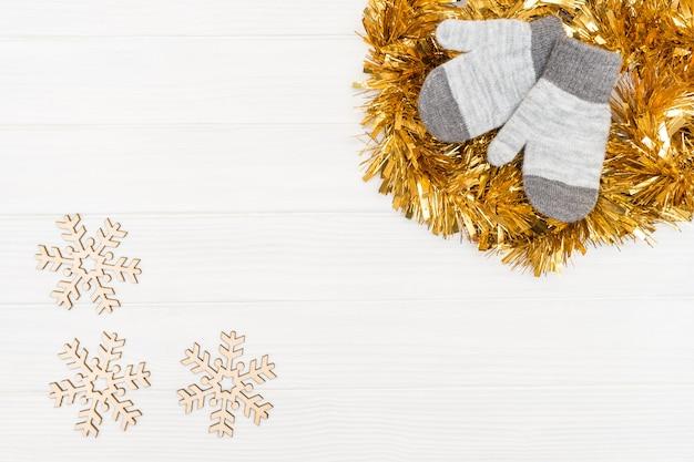 Gants d'hiver avec des flocons de neige en bois sur bois blanc