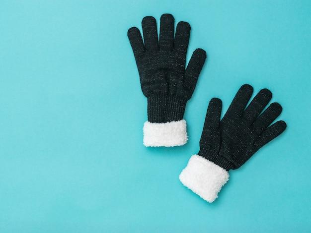 Gants d'hiver pour femmes en tricot avec fourrure sur fond bleu. accessoires d'hiver. mise à plat.