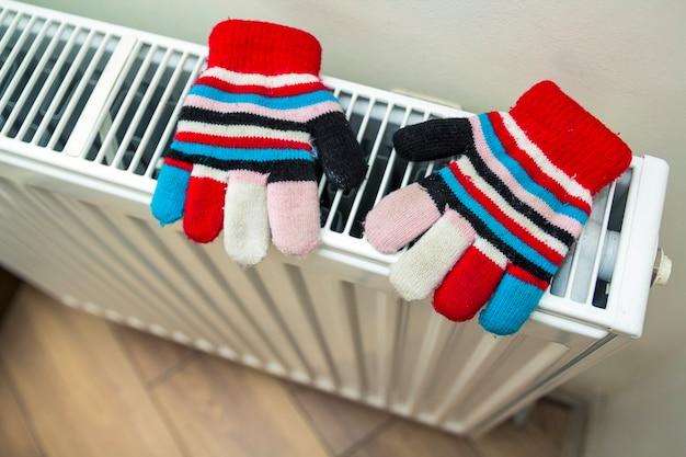 Gants en laine à rayures tricotées à la main pour enfants séchant sur hea