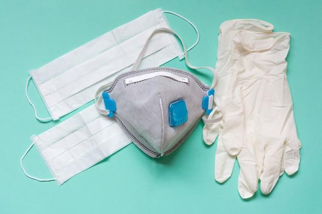 Gants en latex blanc et masque facial médicinal sur fond aigue-marine. protection contre les pandémies, covid-19