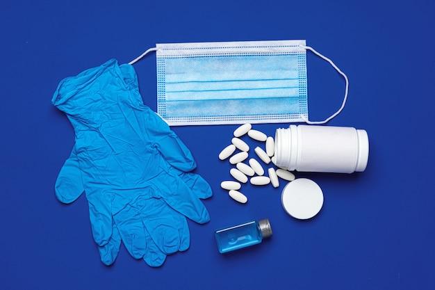 Gants en latex avec masque médical et pilules sur bleu
