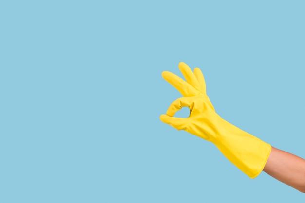 Gants à la main avec signe ok geste sur fond bleu