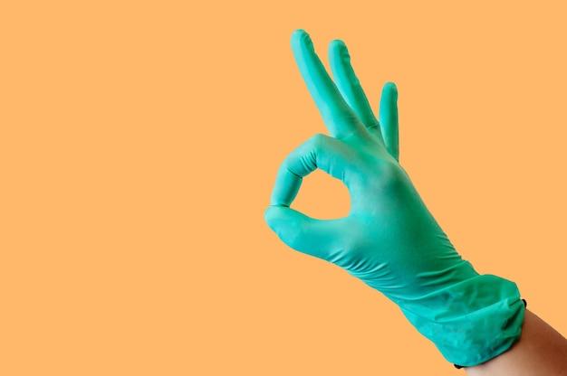 Gants médicaux en latex bleu sur une main féminine, montre un geste ok