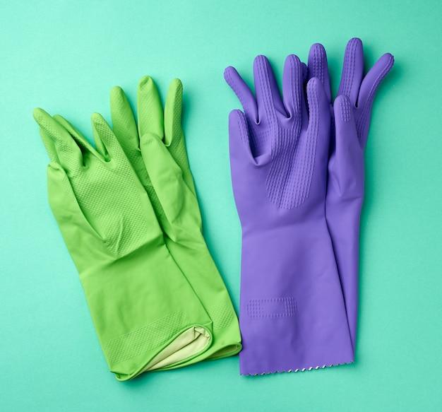 Gants de nettoyage en caoutchouc vert et violet sur une surface verte