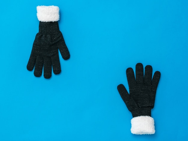Gants noirs tricotés avec fourrure blanche sur fond bleu. accessoires pour femmes par temps froid.
