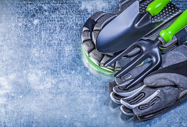 Gants de protection de jardinage protecteurs de genou pelle à main fourche truelle sur fond métallique concept agricole.