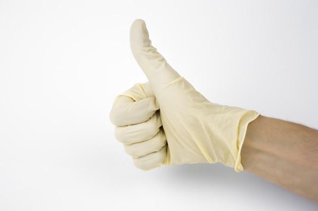 Gants de protection médicaux en latex sur une main masculine sur fond blanc