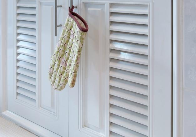 Les gants résistants à la chaleur au motif de feuilles sont suspendus à la poignée de l'armoire