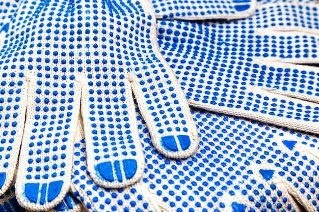 Gants de travail minces avec bouton bleu.