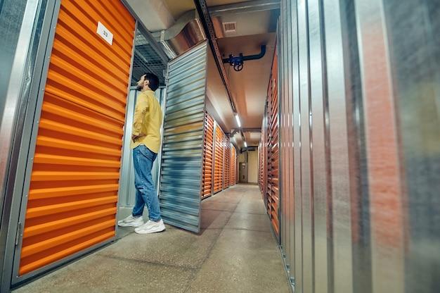 Garage, entrée. homme intéressé dans des vêtements décontractés entrant dans la porte de garage ouverte dans un entrepôt moderne illuminé