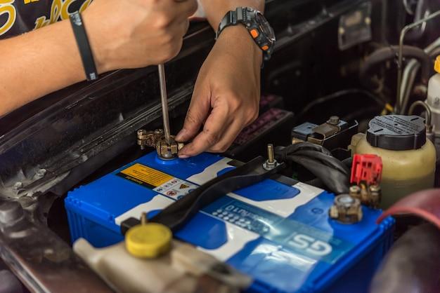 Garagiste ou technicien vérifiant une batterie de voiture