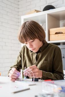 Garçon de 12 ans la construction d'une voiture robot assis à la table en jouant avec des lumières