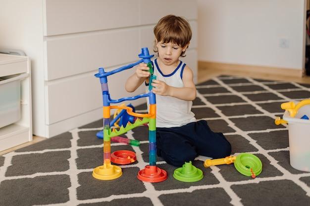 Un garçon de 3 ans se concentre sur l'assemblage du constructeur. développement de la motricité fine et de la réflexion.