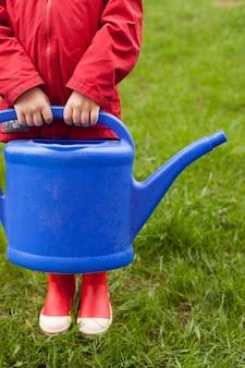 Un garçon de 4 ans dans une veste rouge et des bottes en caoutchouc se prépare à l'arrosage d'un grand arrosoir bleu