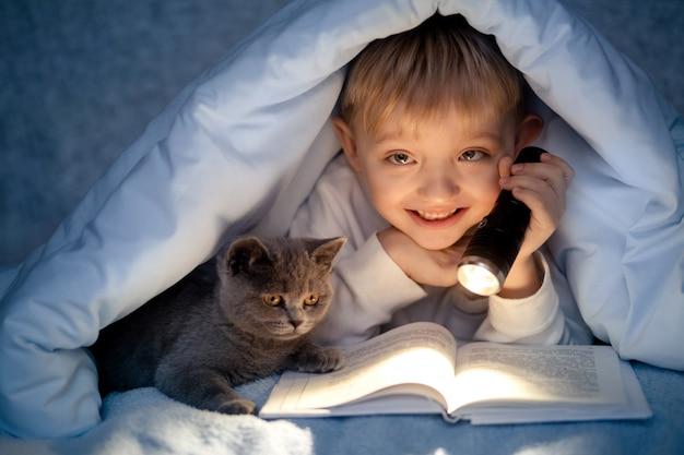 Un garçon de 5 à 6 ans lit un livre le soir dans l'obscurité sous une couverture avec un chaton gris britannique.