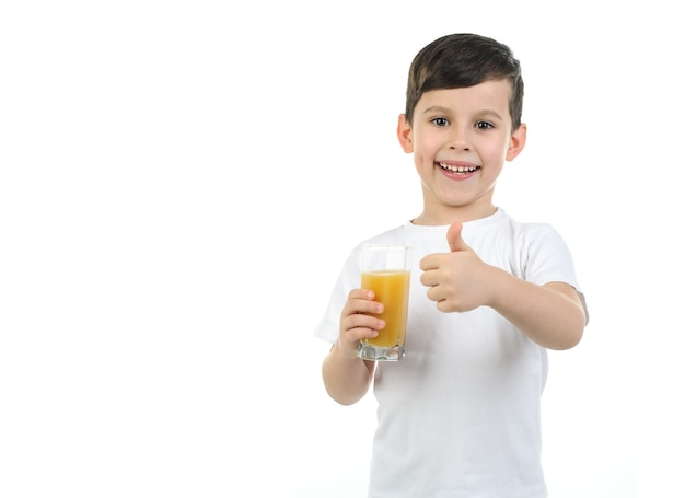 Un garçon de 6 ans dans un t-shirt blanc tient un verre de jus d'agrumes sur fond blanc. fond isolé.
