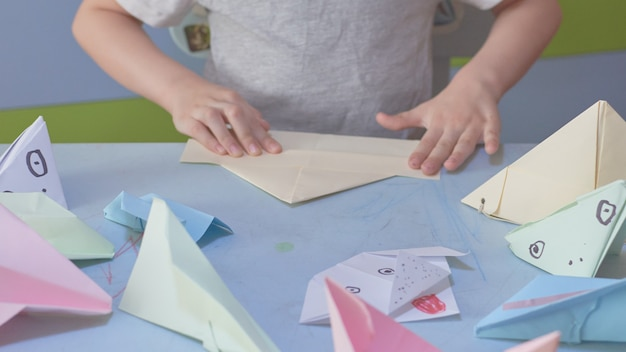 Un garçon de 6 ans fabrique des avions et des grenouilles en origami pendant la quarantaine covid-19, l'auto-isolement, le concept d'éducation en ligne, l'enseignement à domicile. enfant à la maison, jardin d'enfants fermé, art pour enfants.