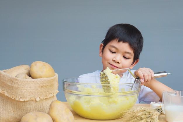 Garçon de 7 ans préparant une purée de pommes de terre avec joie