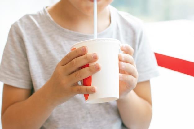 Un garçon de 8 ans boit un cocktail de lait dans une tasse en papier, concept de restauration rapide